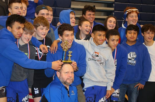North Mason's wrestling team places the team trophy on head coach Bill McCarty's head after winning Saturday's Olympic League 2A sub-regional tournament in Belfair.