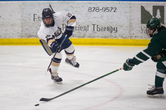 Essex's Tobias Martin, left, passes the puck past the stick of a Rice player during a high school boys hockey game in Essex on Saturday, Feb. 8, 2020.