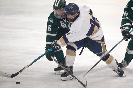 Rice's Jackman Hickey, left, and Essex's Ryan Clark battle for the puck during a high school boys hockey game in Essex on Saturday, Feb. 8, 2020.
