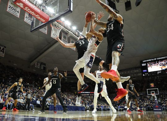 Feb 9, 2020; Storrs, Connecticut, USA; Cincinnati Bearcats center Chris Vogt (33) and guard Jarron Cumberland (34) defend against Connecticut Huskies guard James Bouknight (2) in the first half at Harry A. Gampel Pavilion.