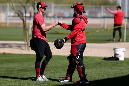 Cincinnati Reds pitcher Sonny Gray, left, and catcher Tucker Barnhart fist bump as pitchers and catchers participate in informal workouts on report day, Tuesday, Feb. 12, 2019, at the Cincinnati Reds spring training facility in Goodyear, Arizona.