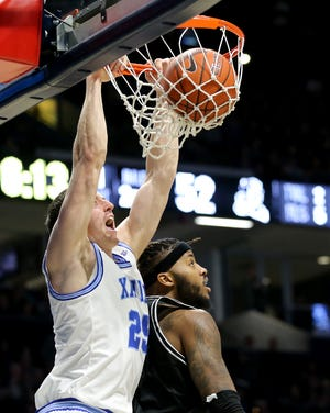Xavier Musketeers forward Jason Carter (25) dunks as Providence Friars center Nate Watson (0) defends in the second half during a college basketball game, Saturday, Feb. 8, 2020, at Cintas Center in Cincinnati. Xavier won 64-58.