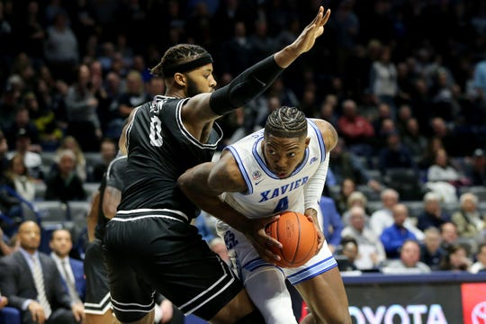 Xavier Musketeers forward Tyrique Jones (4) spins toward the basket as Providence Friars center Nate Watson (0) defends in the second half during a college basketball game, Saturday, Feb. 8, 2020, at Cintas Center in Cincinnati. Xavier won 64-58.
