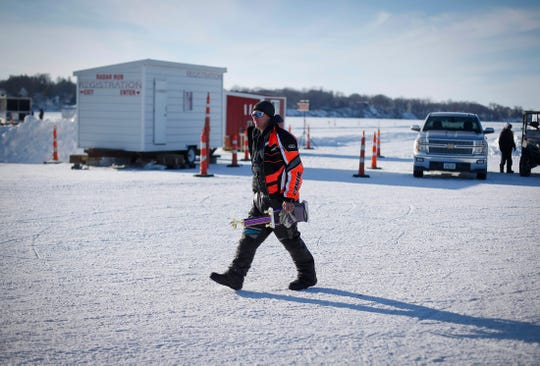 A snowmobile rider walks away with a large trophy during the Midwest Sled Fest in Clear Lake on Saturday, Feb. 8, 2020.