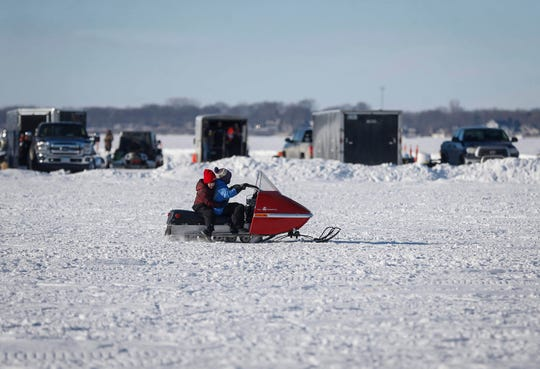 A pair of young snowmobile enthusiasts ride on an old snowmobile during the Midwest Sled Fest in Clear Lake on Saturday, Feb. 8, 2020.