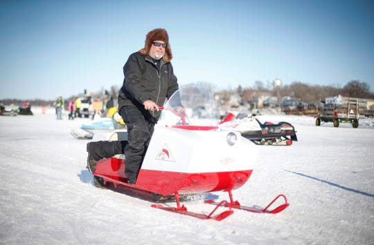 A snowmobile rider operates an old snowmobile across the ice of Clear Lake during the Midwest Sled Fest in Clear Lake on Saturday, Feb. 8, 2020.