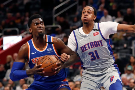 New York Knicks forward Bobby Portis, left, looks towards the basket as Detroit Pistons forward John Henson (31) defense during the first half of an NBA basketball game, Saturday, Feb. 8, 2020, in Detroit.
