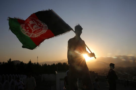 FILE - In this Aug. 19, 2019, file photo, a man waves an Afghan flag during Independence Day celebrations in Kabul, Afghanistan.