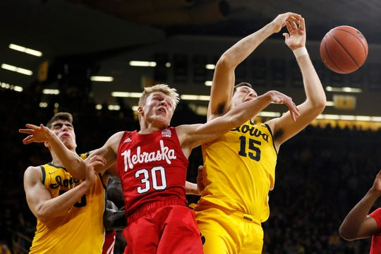 Nebraska guard Charlie Easley (30) fights for a rebound with Iowa's Luka Garza, left, and Ryan Kriener, right, during the second half.