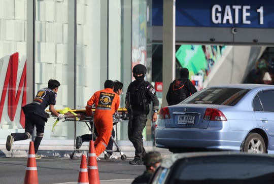 Medics carry a stretcher toward Terminal 21 Korat mall as commando soldiers work the scene of a shooting at the mall in Nakhon Ratchasima, Thailand, Sunday, Feb. 9, 2020.