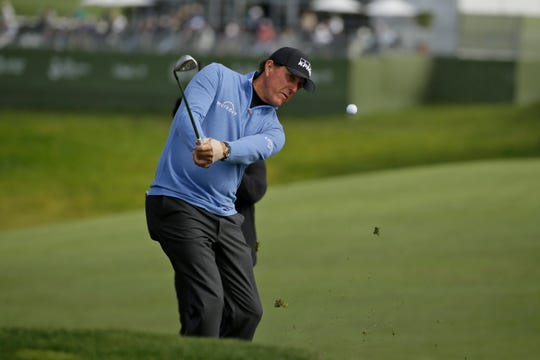 Phil Mickelson chips the ball up to the sixth green.