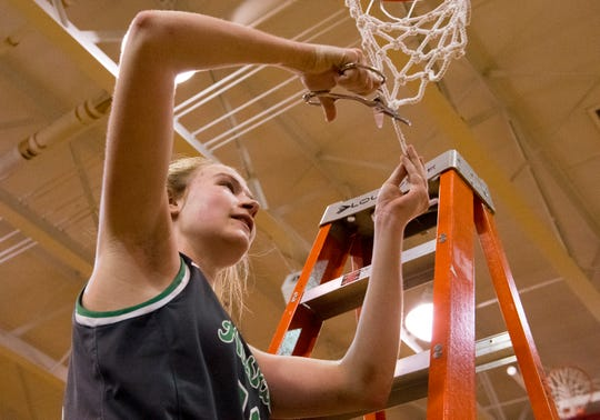North's Kenna Hisle (12) cuts down the net after beating the Castle Knights in the HSAA Class 4A girls basketball sectional championship game at Harrison High School Saturday evening, Feb. 8, 2020. North Lady Huskies won 56-44.
