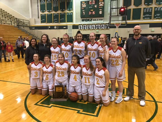 The Mater Dei girls basketball team celebrates following their 56-52 sectional championship victory over Forest Park.