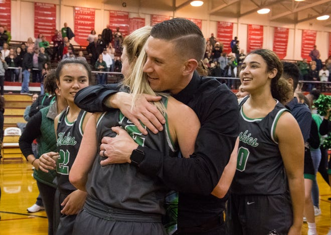 North girls' coach Tyler Choate hugs Kenna Hisle (12) after the Huskies won their third sectional championship in school history last Saturday.