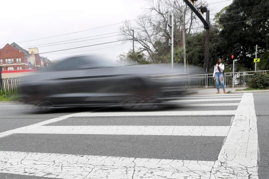 A student stands in the median of West Tennessee Street, waiting to cross in the crosswalk between Stadium Drive and Woodward Avenue, as cars speed past Wednesday, Feb. 5, 2020. Natalie Nickchen, an FSU student, was killed in the crosswalk after being hit by a car last week.