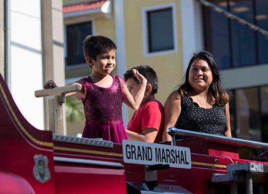 Sarai Salinas-Hernandez, 7, left, waves to the crowd while riding in a fire truck with her mom Adele and brother Kevin in the 2020 Edison Festival of Light Junior Parade on Sunday, Feb. 9, 2020. Sarai was the parade's Grand Marshal.