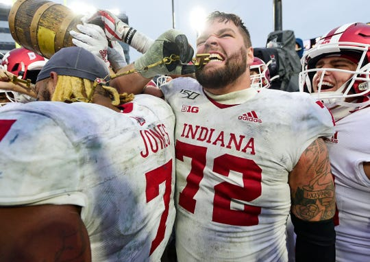 Nov 30, 2019; West Lafayette, IN, USA; Indiana Hoosiers offensive lineman Simon Stepaniak (72)  bites one of the letters from the Old Oaken Bucket after the Hoosiers  defeated the Purdue Boilermakers, 44-41, in 2 OT at Ross-Ade Stadium.