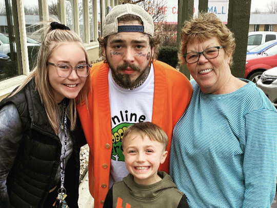Post Malone poses for a photo with Madigan Pea, left, Cohen Neat and Margo Blair Harczynski Saturday at Olive Garden, 8155 E. Washington St.