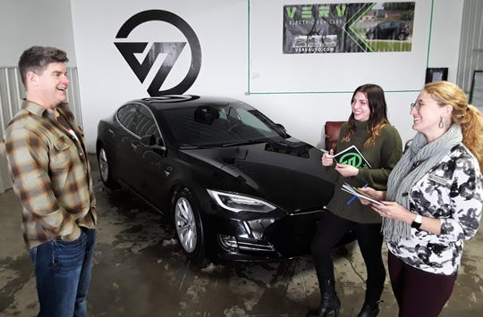VERV CEO and owner Jason Hall jokes with his two employees Tessa Meyer (left) and Leah Furnish next to the premier vehicle in their current used electric car inventory – a sleek, black 2018 Tesla Model S. The owner says the dealership is a logical spin-off from his Moxie Solar company in North Liberty.