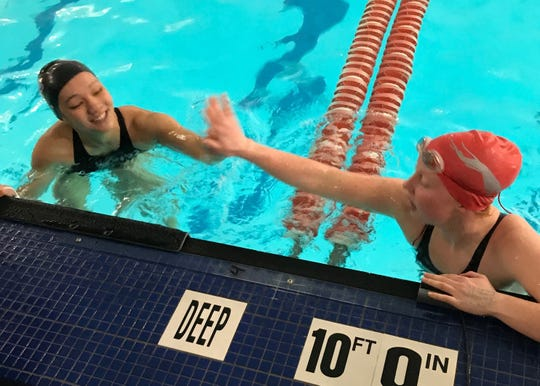 Ontario's Amy Evans (left) and Shelby's Rylie White slap palms after battling in the 100 butterfly in Saturday's Division II sectional swim meet.