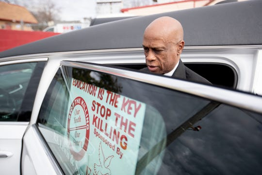 Ike Fisher of R.S. Lewis and Sons funeral home, puts a sign in the window of his hearse Sunday, Feb. 9, 2020, before the State of Emergency Ride in Memphis.