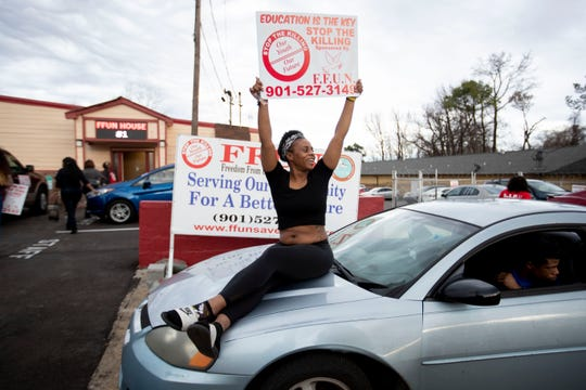 Eunicia Alexander waives a sign at passing by motorists in front of the F.F.U.N building Sunday, Feb. 9, 2020, after the State of Emergency Ride in Memphis.
