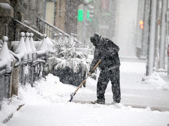 A worker at the Hilton Garden Inn in downtown Milwaukee clears snow from the sidewalk in front of the hotel on Sunday.