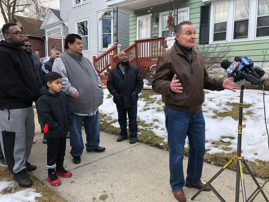Ald. Bob Donovan speaks to reporters outside his home Saturday afternoon about gun violence in Milwaukee. Behind him are faith leaders in Milwaukee, who are banding together to make a change in the city.