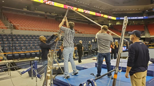 Auburn Arena operations manager Darryl Maddox (left) and his crew take down the uneven bars after gymnastics meet on Friday, Feb. 7, 2020.