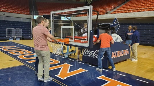 Auburn Arena operations manager Darryl Maddox and student workers put one of the basketball hoops in place after a gymnastics meet on Friday, Feb. 7, 2020.