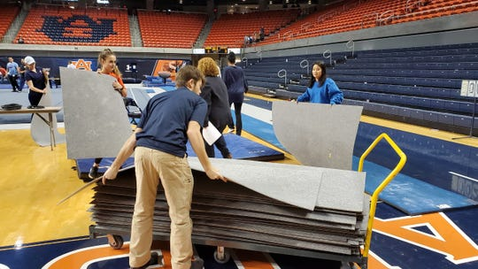 Student workers stack the mats that sit underneath the gymnastics equipment on Friday, Feb. 7, 2020.