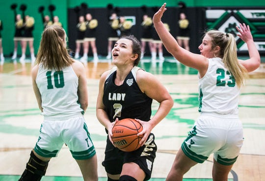 Winchester's Maddie Lawrence slips past Yorktown's defense during their sectional championship game at Yorktown High School Saturday, Feb. 8, 2020.