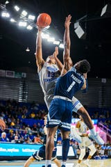 MTSU's Jayce Johnson (13) puts up a layup over Rice's Josh Parrish during Saturday's game.