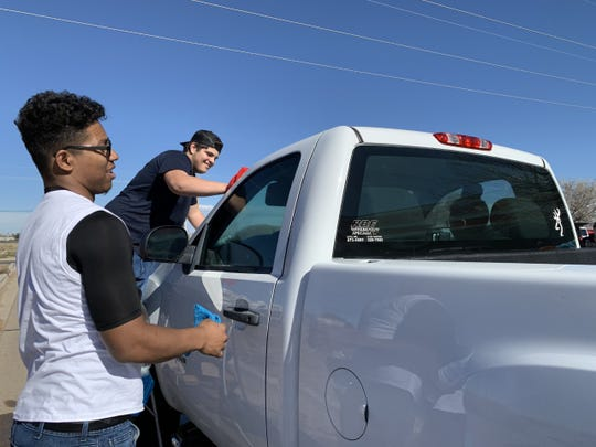 Neo Quinones, left, whose cousin and Oñate football teammate Luis Mendez was killed in a car crash, helps family and friends wash cars at a benefit fundraiser Sunday, Feb. 9, 2020 at the Auto Zone on Bataan Memorial East. Luis, 18, was killed, on Saturday, Feb. 8.