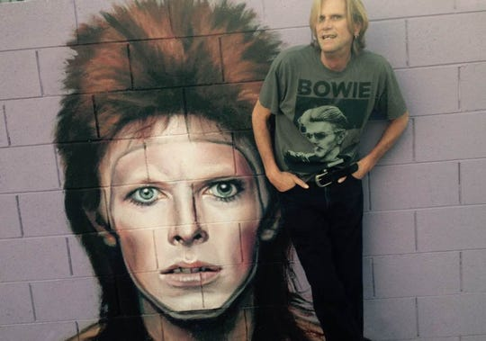 Richard Flower posing in front of Maggie Keane's mural paying tribute to one of Flower's heroes, David Bowie.