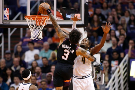Phoenix Suns forward Kelly Oubre Jr. (3) dunks next to Denver Nuggets forward Paul Millsap (4) during the second half of an NBA basketball game Saturday, Feb. 8, 2020, in Phoenix. (AP Photo/Ralph Freso)