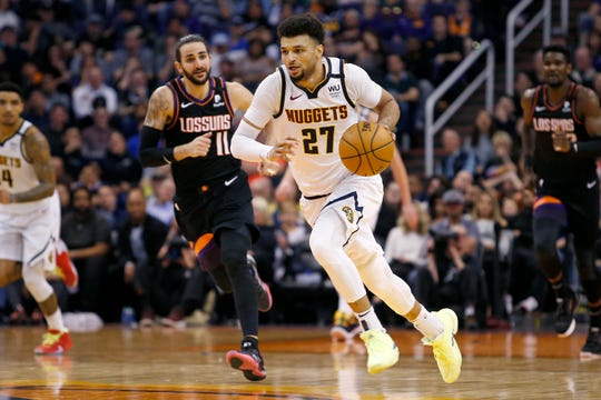 Denver Nuggets guard Jamal Murrey brings the ball up ahead of Phoenix Suns' Ricky Rubio (11) during the second half of an NBA basketball game Saturday, Feb. 8, 2020, in Phoenix. (AP Photo/Ralph Freso)