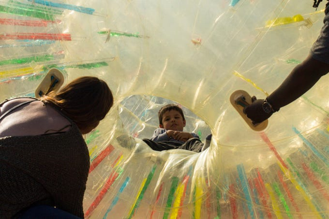 Eli Armijo, 4, is coaxed out of an inflatable ball toy during during the Chinese Culture and Cuisine Festival on Feb. 8, 2020, at Margaret T. Hance Park.