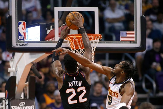 Phoenix Suns center Deandre Ayton (22) dunks against the defense of Denver Nuggets forward Jerami Grant (9) during the first half of an NBA basketball game, Saturday, Feb. 8, 2020, in Phoenix. (AP Photo/Ralph Freso)