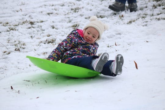 Grace Skidmore, of Toledo, enjoys sledding down the hill at Twin Oast during their Winter Fest on Saturday.