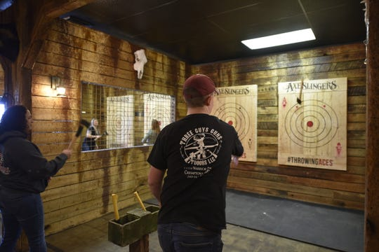 Will Strait, right, and Bobbi Jo Shoop each throw an axe at a target at Axe Slingers on Saturday, Feb. 8, 2020.