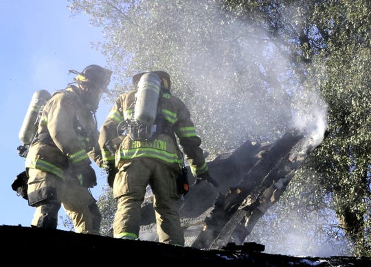 Redding firefighters tear apart the smoldering roof of a home on Alrose Lane that caught fire Saturday afternoon.