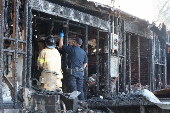 Redding fire inspector Mike Ham, left, and battalion chief J.T. Zulliger of the California Department of Forestry and Fire Protection investigate Saturday's fire at 1440 Alrose Lane. Zulliger happened to be in the area during the blaze and assisted in the investigation.