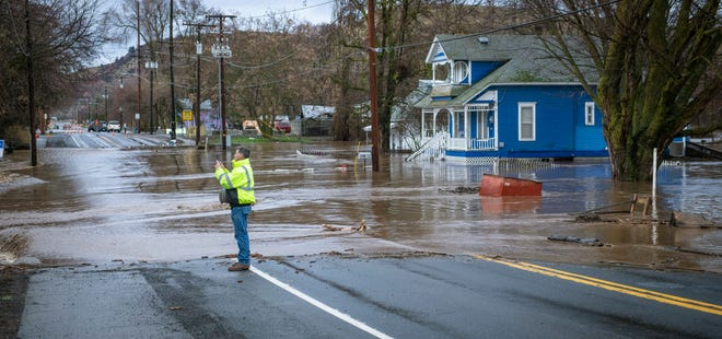 Touchet River water flows across Highway 12, closing it, on the east side of Waitsburg, Washington, on Friday, Feb. 7, 2020. (Greg Lehman/Walla Walla Union-Bulletin via AP)