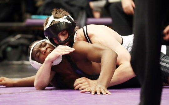 From right, John Jay (CR) Gavin Fiacco on his way to defeating New Rochelle's Steven Burrell in the 160-pound weight class during the divisional wrestling tournament at John Jay High School in Cross River Feb. 8, 2020.