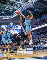 Rhode island's Jacob Toppin blocks a shot in a game against the Providence Friars.