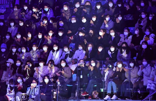 Spectators wear face masks to help prevent the spread of the coronavirus virus that originated in central China as they watch the exhibition gala at the ISU Four Continents Figure Skating Championships in Seoul on Feb. 9, 2020.