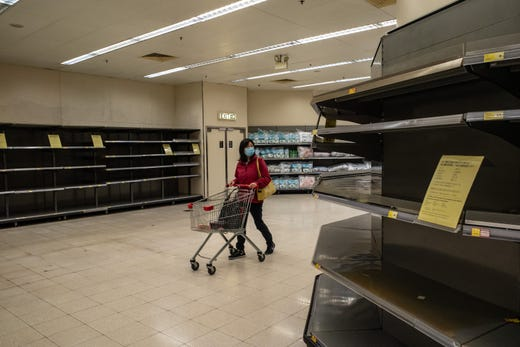 A shopper wearing face mask pushes a shopping cart in front of an empty shelves inside a grocery store on Feb. 9, 2020 in Hong Kong, China. Hong Kong has 29 confirmed cases of Novel coronavirus (2019-nCoV), with over 37,500 confirmed cases around the world, the virus has so far claimed over 800 lives.
