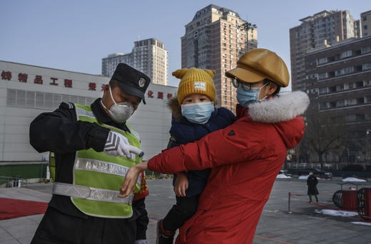 A Chinese woman wears a protective mask as she has her temperature checked before entering a park with her child  on Feb. 9, 2020 in Beijing, China. The number of cases of a deadly new coronavirus rose to more than 37000 in mainland China Sunday, days after the World Health Organization (WHO) declared the outbreak a global public health emergency. China continued to lock down the city of Wuhan in an effort to contain the spread of the pneumonia-like disease which medicals experts have confirmed can be passed from human to human. In an unprecedented move, Chinese authorities have put travel restrictions on the city which is the epicenter of the virus and municipalities in other parts of the country affecting tens of millions of people. The number of those who have died from the virus in China climbed to over 810 on Sunday, mostly in Hubei province, and cases have been reported in other countries including the United States, Canada, Australia, Japan, South Korea, India, the United Kingdom, Germany, France and several others. The World Health Organization has warned all governments to be on alert and screening has been stepped up at airports around the world. Some countries, including the United States, have put restrictions on Chinese travelers entering and advised their citizens against travel to China.