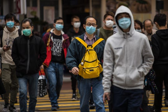 People wearing protective face masks cross a street in Hong Kong on Feb. 9, 2020, as a preventative measure after a coronavirus outbreak which began in the Chinese city of Wuhan. The previously unknown virus has caused alarm because of its similarity to SARS (Severe Acute Respiratory Syndrome), which killed hundreds across mainland China and Hong Kong in 2002-2003.